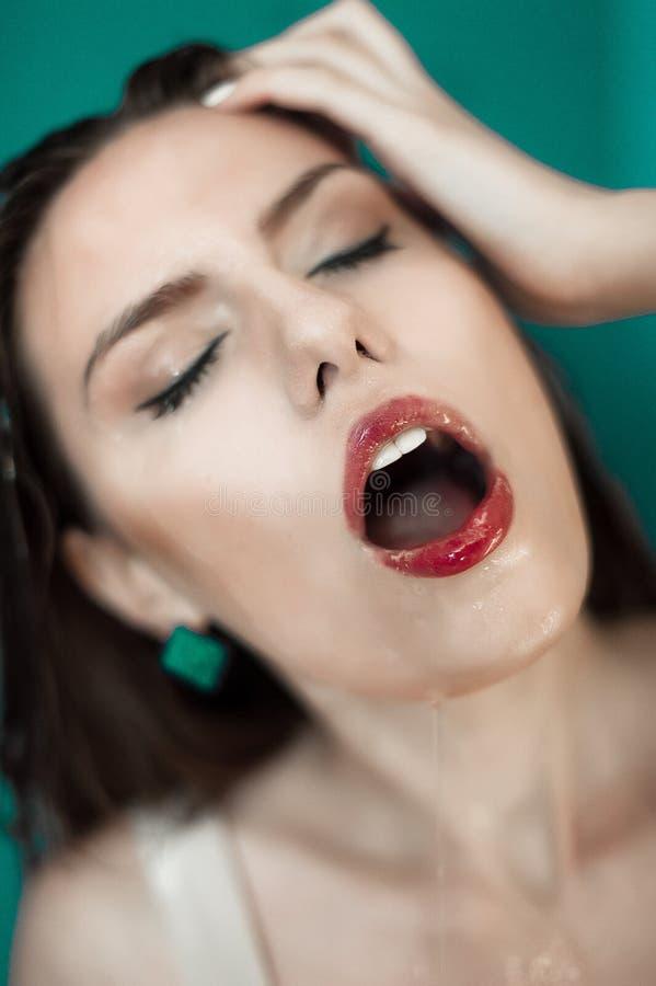Close-up da face molhada bonita da mulher com gota da água No fundo verde fotos de stock royalty free