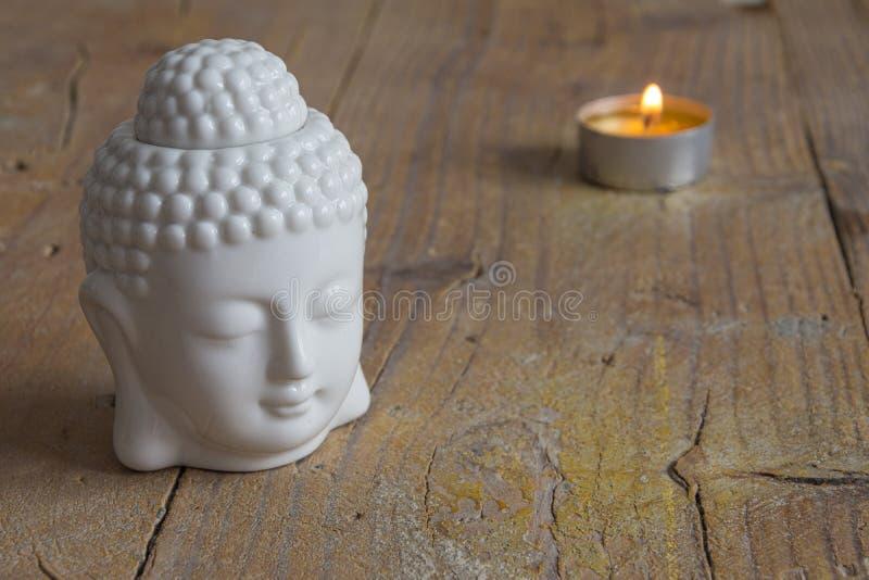 Close-up da figura e da vela brancas de buddha na placa de madeira resistida imagens de stock royalty free