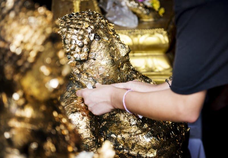 Close up da folha da folha de ouro do gilding de mãos à estátua da Buda no templo tailandês fotos de stock royalty free