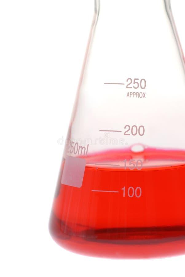 Close up da garrafa cónica de vidro com líquido vermelho imagem de stock