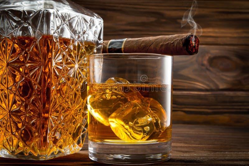 Close up da garrafa, do vidro com uísque e do charuto ardendo sem chama fotos de stock royalty free