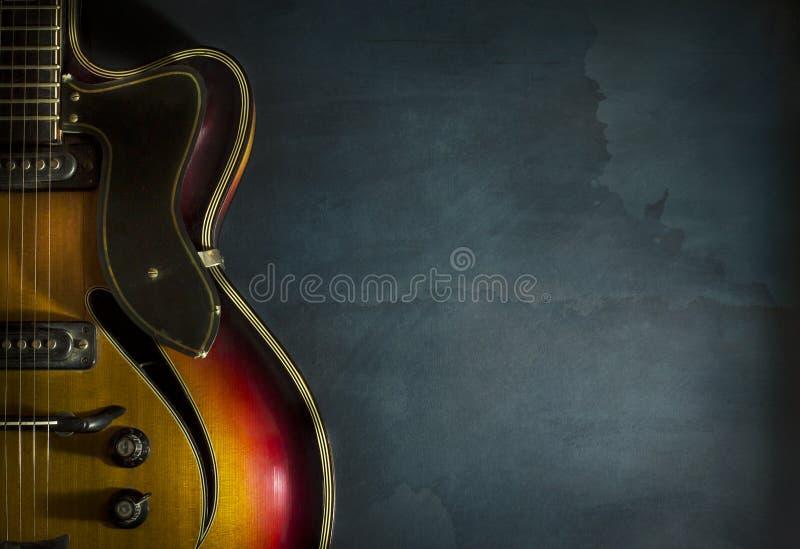 Close-up da guitarra elétrica velha em uma obscuridade - fundo azul do jazz fotografia de stock