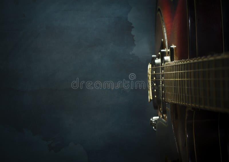Close-up da guitarra elétrica velha em uma obscuridade - fundo azul do jazz fotos de stock
