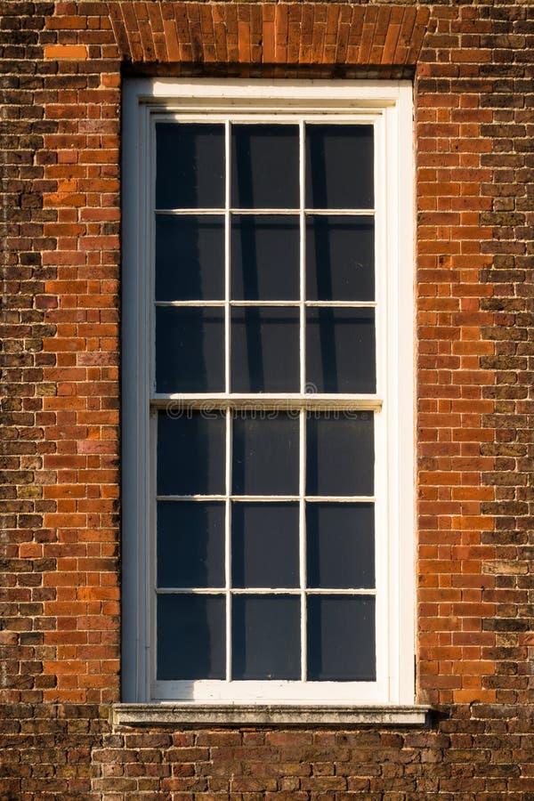Close-up da janela branca na parede de tijolo vermelha da construção de Tudor imagem de stock