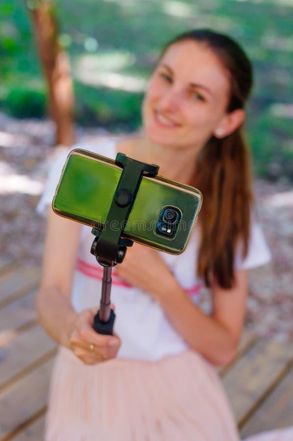 Close up da jovem mulher de sorriso que toma o selfie no usin esperto do telefone imagem de stock