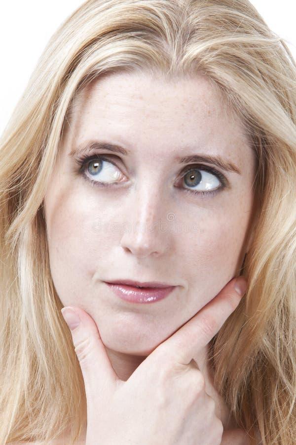 Close-up da jovem mulher pensativa com mão no queixo que olha afastado fotos de stock