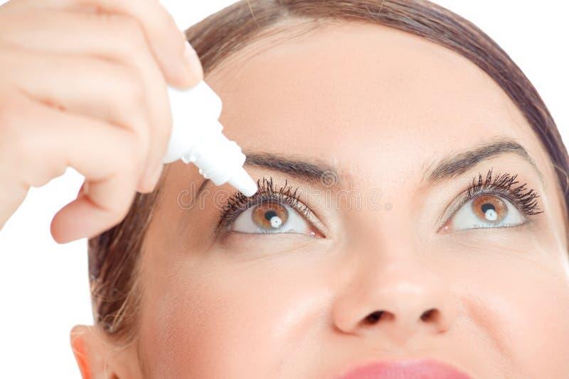 Close up da jovem mulher que aplica as gotas de olho, foco seletivo somente no olho direito imagem de stock