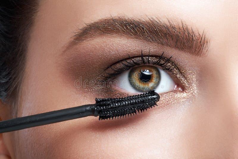 Close-up da jovem mulher que aplica o rímel nas pestanas pelo cosmeti fotografia de stock