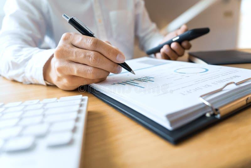 Close-up da leitura do homem de negócios das mãos e escrita com contrato de assinatura da pena sobre o documento para terminar o  fotografia de stock