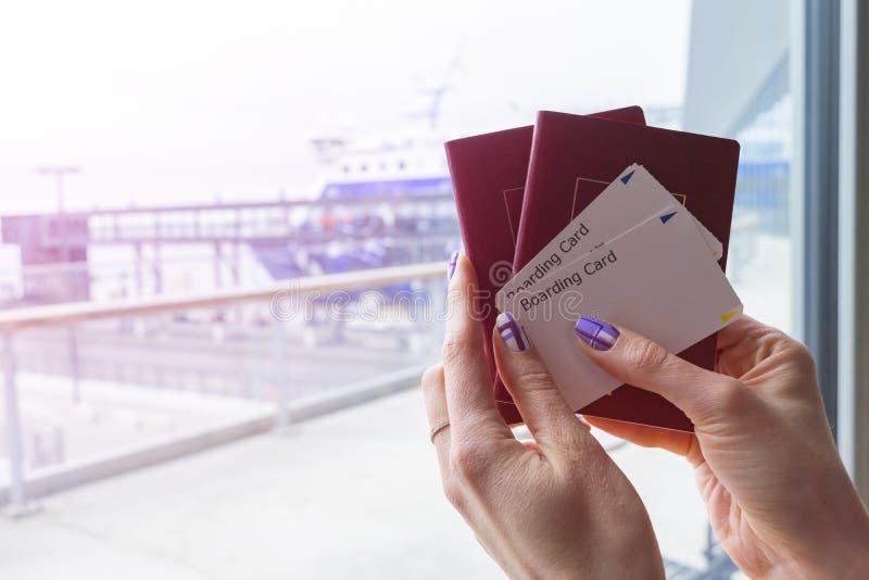 Close up da mão bonita da mulher que guarda passaportes e bilhetes da passagem de embarque no terminal de aeroporto Conceito do c imagens de stock royalty free