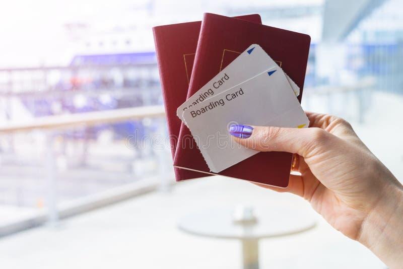 Close up da mão bonita da mulher que guarda passaportes e bilhetes da passagem de embarque no terminal de aeroporto Conceito do c foto de stock royalty free
