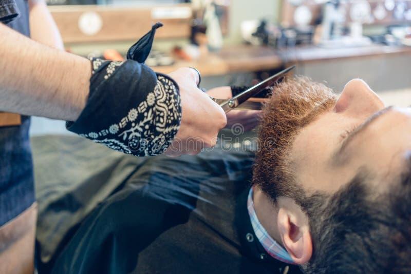 Close-up da mão de um barbeiro que usa tesouras ao aparar foto de stock royalty free