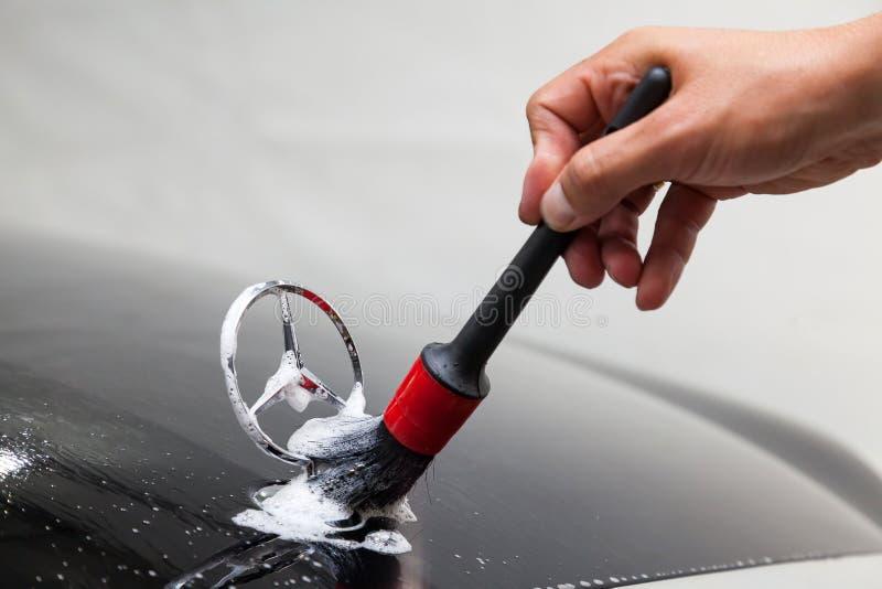 Close-up da mão de um homem com uma escova ao limpar o emblema de um carro de Mercedes-Benz na capa de um carro preto ao lavar fotografia de stock royalty free