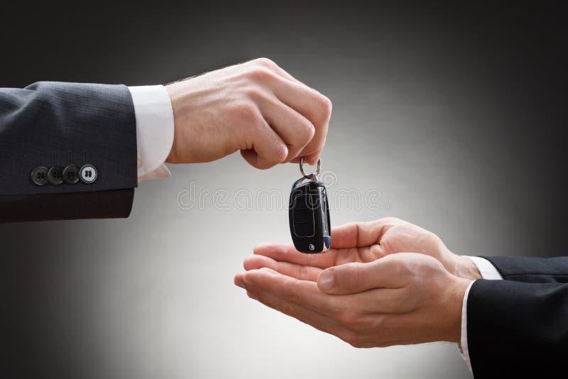 Close-up da mão de um homem de negócios que dá a chave do carro imagem de stock