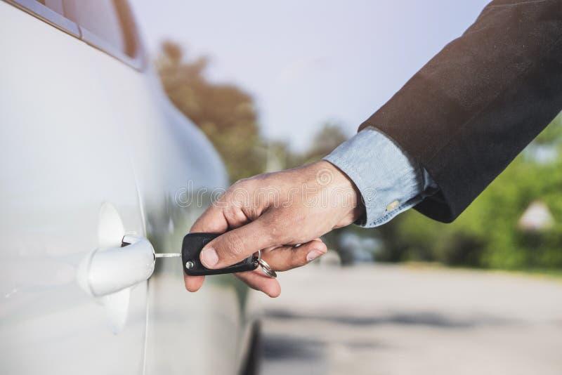 Close up da mão de um homem que introduz uma chave na fechadura da porta de um carro Formato horizontal O carro e o homem são irr fotografia de stock royalty free
