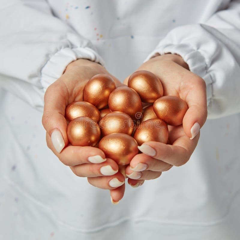 Close-up da mão de uma menina que guarda muitos ovos dourados coloridos na perspectiva de um avental branco Conceito da riqueza fotos de stock