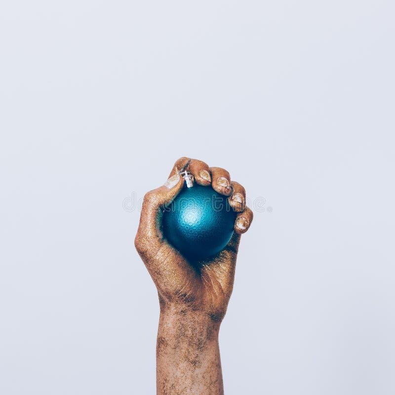 Close-up da mão de uma mulher na pintura dourada que guarda Cristo azul foto de stock royalty free