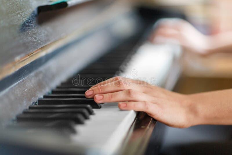 Close-up da mão de uma mulher que jogue o piano foto de stock