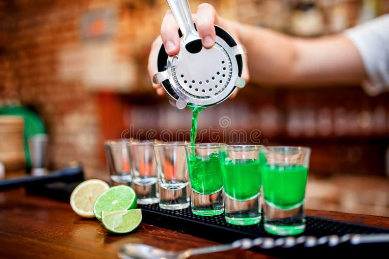 Close-up da mão do barman que derrama a bebida alcoólica fotografia de stock royalty free
