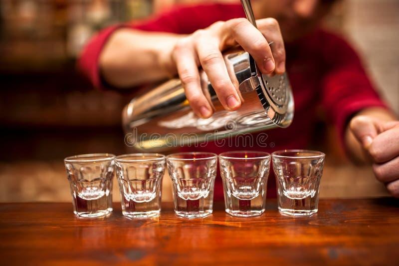 Close-up da mão do barman que derrama a bebida alcoólica no clube noturno, fotografia de stock royalty free