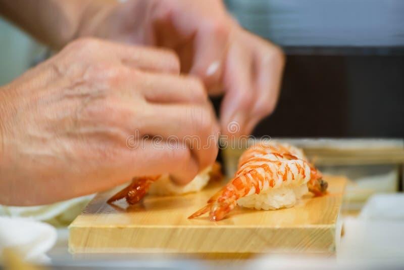 Close up da mão do cozinheiro chefe de sushi japonês fotografia de stock