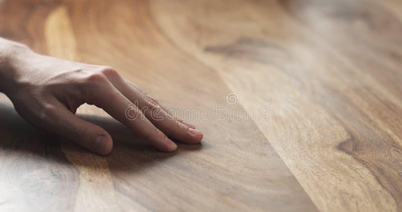 Close up da mão do homem que verifica a superfície dura da madeira imagem de stock