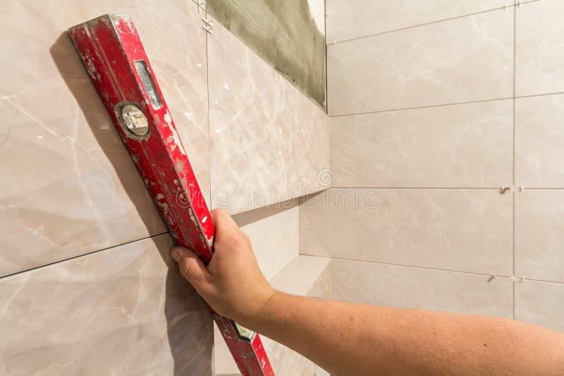 Close-up da mão do tiler do trabalhador com a alavanca que instala em azulejos das paredes Telha a instalação, ferramentas e melh imagem de stock