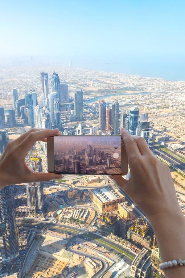 Close up da mão do turista da mulher que toma a foto da cidade de Dubai com a câmera do smartphone da torre de Burj Khalifa foto de stock