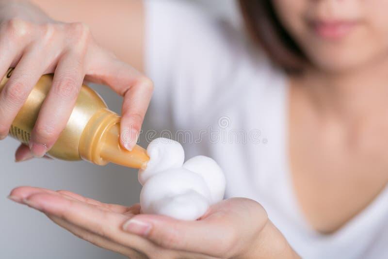 Close-up da mão fêmea do barbeiro do cabeleireiro com musse de cabelo imagens de stock royalty free