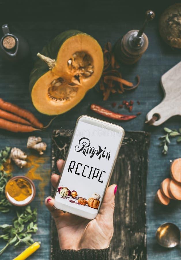 Close up da mão fêmea usando o smartphone com o texto que rotula a receita da abóbora na mesa de cozinha com abóbora e ingredient fotos de stock