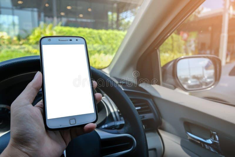 Close-up da mão masculina do motorista usando o smartphone no carro no dia ensolarado imagens de stock