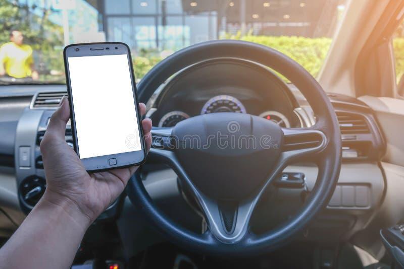 Close-up da mão masculina do motorista usando o smartphone no carro no dia ensolarado fotos de stock