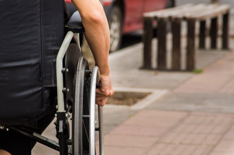Close-up da mão masculina na roda da cadeira de rodas durante a caminhada no parque imagem de stock royalty free