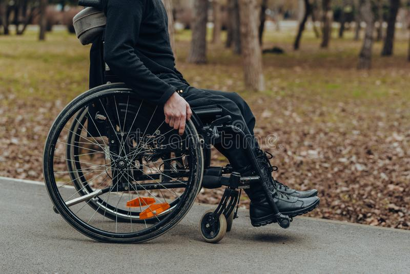 Close-up da mão masculina na roda da cadeira de rodas durante a caminhada no parque imagens de stock royalty free