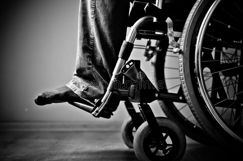 Close-up da mão masculina na roda da cadeira de rodas imagem de stock