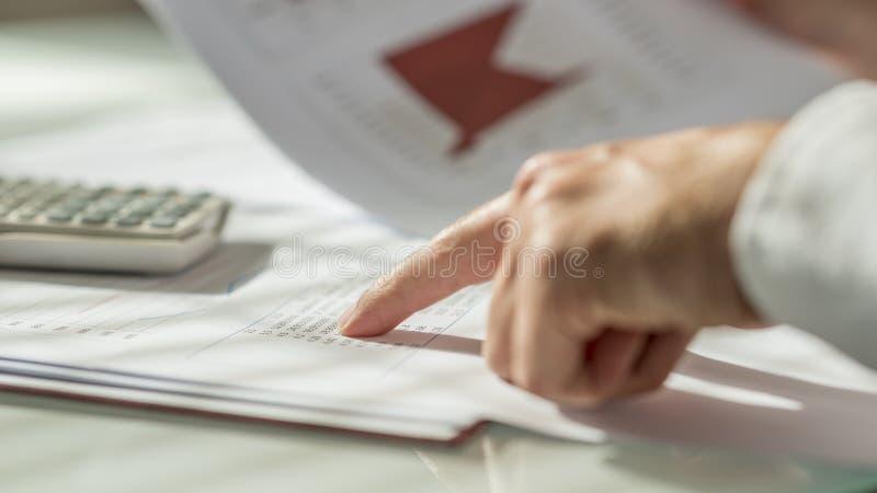 Close up da mão masculina que aponta às figuras redigidas em um original fotografia de stock