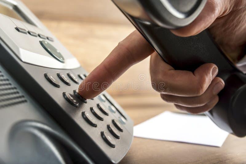 Close up da mão masculina que disca um número de telefone no landlin preto imagens de stock