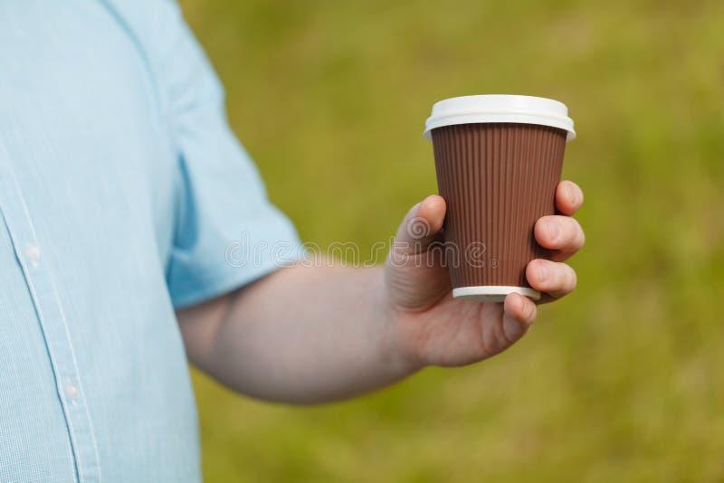 Close-up da mão masculina que guarda o café para levar embora foto de stock royalty free