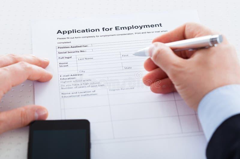 Close-up da mão que guarda Pen Over Employment Application imagem de stock