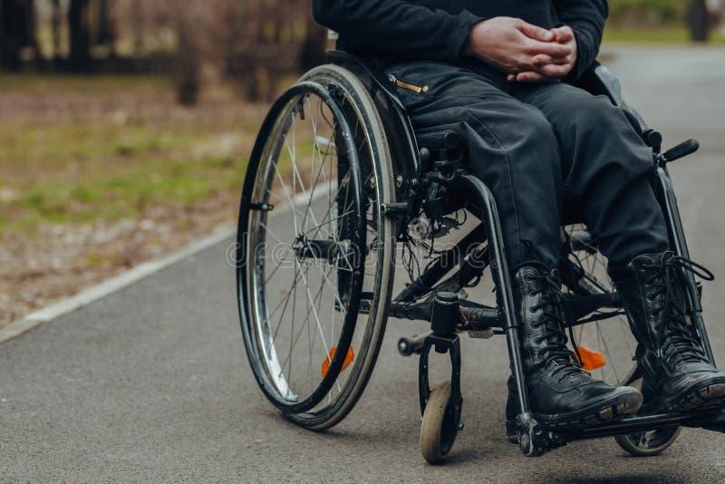 Close-up da m?o masculina na roda da cadeira de rodas durante a caminhada no parque imagem de stock royalty free