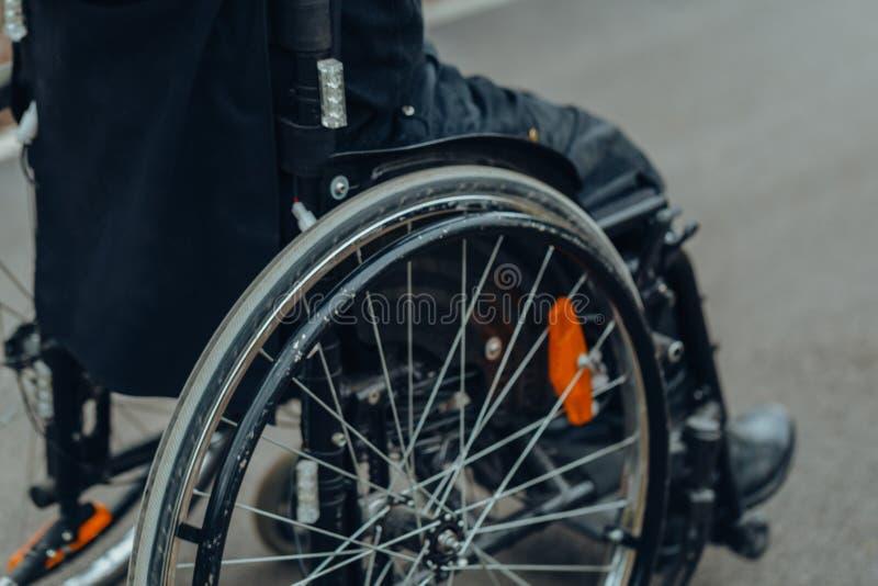 Close-up da m?o masculina na roda da cadeira de rodas durante a caminhada no parque foto de stock