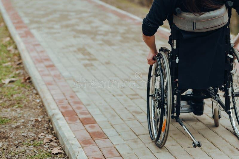 Close-up da m?o masculina na roda da cadeira de rodas durante a caminhada no parque imagens de stock