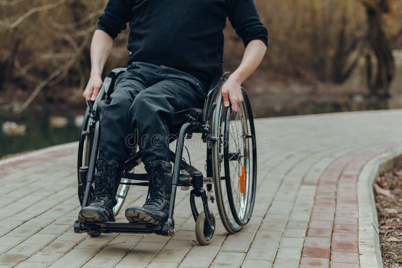 Close-up da m?o masculina na roda da cadeira de rodas durante a caminhada no parque fotos de stock