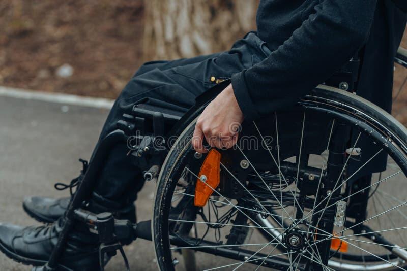 Close-up da m?o masculina na roda da cadeira de rodas durante a caminhada no parque foto de stock royalty free
