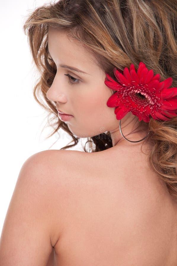 Close-up da menina bonita com a flor vermelha do áster fotografia de stock