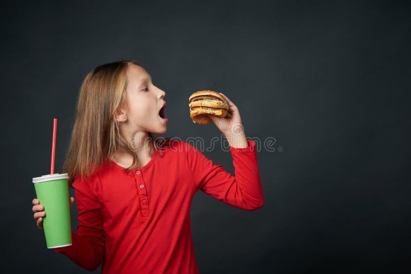 Close up da menina com fome que olha para a frente para morder um Hamburger imagens de stock royalty free