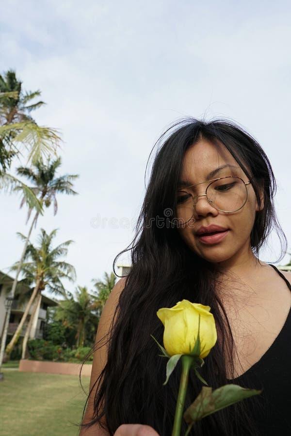 Close-up da menina com vidros, guardando a flor cor-de-rosa amarela fotos de stock royalty free