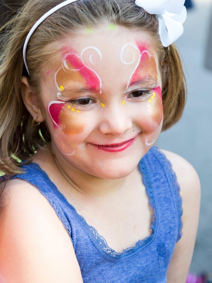 Close up da menina de sorriso bonito com composição da cara da borboleta imagens de stock royalty free