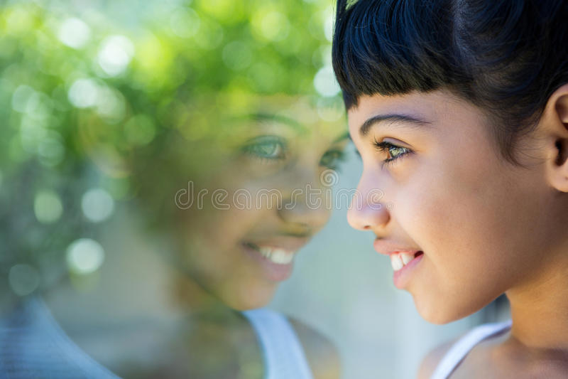 Close-up da menina de sorriso que olha através da janela fotografia de stock royalty free