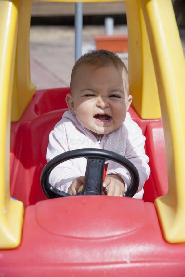 Close-up da menina engraçada que conduz o carro do brinquedo imagens de stock